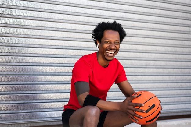 バスケットボールのボールを保持し、屋外に座ってトレーニング後にリラックスしたアフロアスリートの男性の肖像画。スポーツと健康的なライフスタイル。