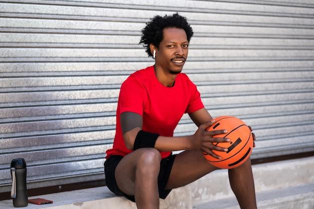 농구 공을 들고 야외에서 앉아있는 동안 훈련 후 휴식 아프리카 선수 남자의 초상화. 스포츠와 건강한 라이프 스타일.