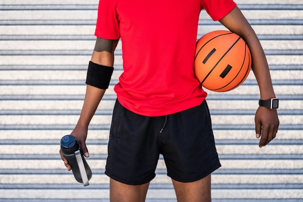 屋外に立っているときにバスケットボールのボールを保持しているアフロアスリートの男の肖像画。スポーツと健康的なライフスタイル。