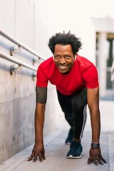 屋外で走る準備をしているスタート位置にいるアフロアスリートの男性の肖像画。スポーツと健康的なライフスタイル。