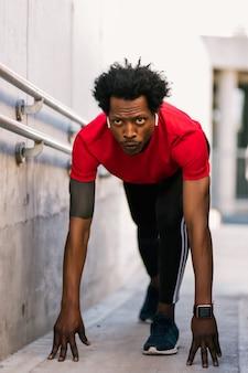 야외에서 실행을 준비하는 시작 위치에 아프리카 선수 남자의 초상화. 스포츠와 건강한 라이프 스타일.