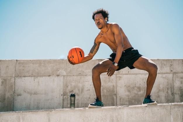 屋外でバスケットボールのボールで遊んで練習しているアフロアスリートの男の肖像画。スポーツと健康的なライフスタイル。