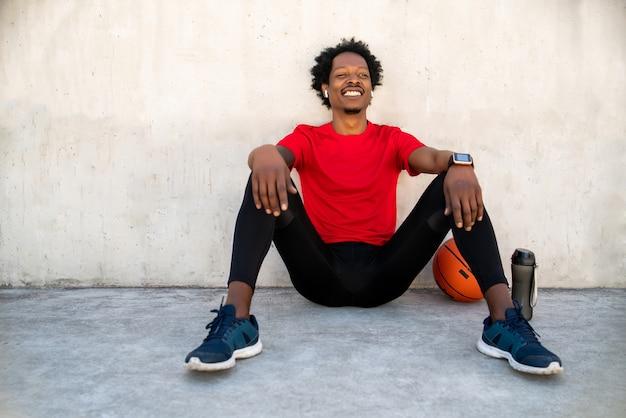 屋外で運動した後、リラックスして床に座っているアフロアスリート男性の肖像画。スポーツと健康的なライフスタイル。
