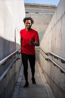 屋外で走って運動をしているアフロアスリート男性の肖像画。スポーツと健康的なライフスタイル。