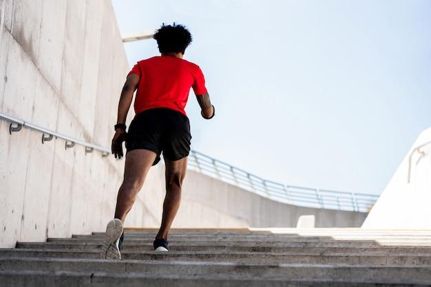 屋外で実行し、運動をしているアフロアスリート男性の肖像画。スポーツと健康的なライフスタイル。