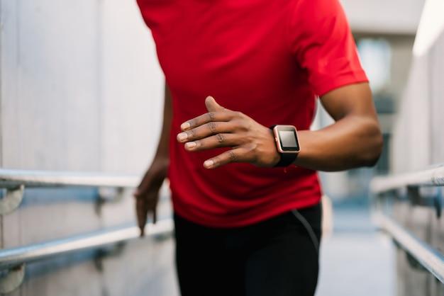 実行し、屋外で運動をしているアフロアスリート男性の肖像画。スポーツと健康的なライフスタイル。 Premium写真