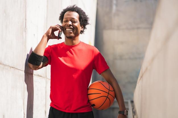 Портрет человека афро-спортсмена разговаривает по телефону и расслабляется после тренировки на открытом воздухе. спорт и здоровый образ жизни.