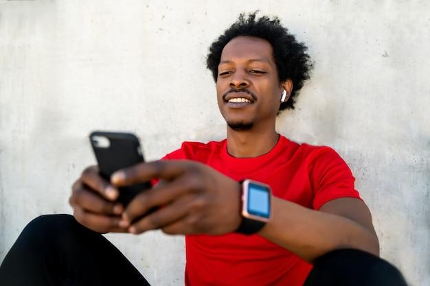 携帯電話を使用して屋外で運動した後にリラックスしたアフロアスリートの男性の肖像画。スポーツと健康的なライフスタイル。