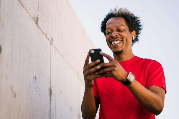 彼の携帯電話を使用して、屋外で運動した後にリラックスしているアフロアスリートの男性の肖像画。