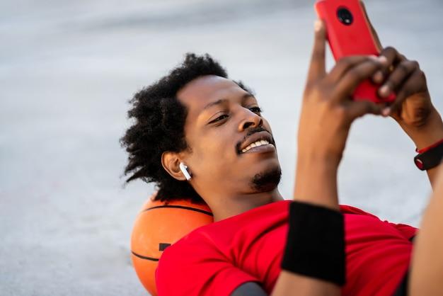 屋外でトレーニングした後、床に横たわっているときに携帯電話を使用しているアフロアスリートの男性の肖像画。スポーツと健康的なライフスタイル。