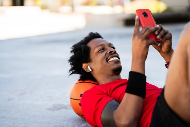 屋外でトレーニングした後、床に横たわっているときに彼の携帯電話を使用してアフロアスリートの男性の肖像画。スポーツと健康的なライフスタイル。