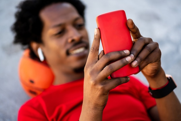 屋外でトレーニングした後、床に横たわっているときに彼の携帯電話を使用してアフロアスリート男性の肖像画