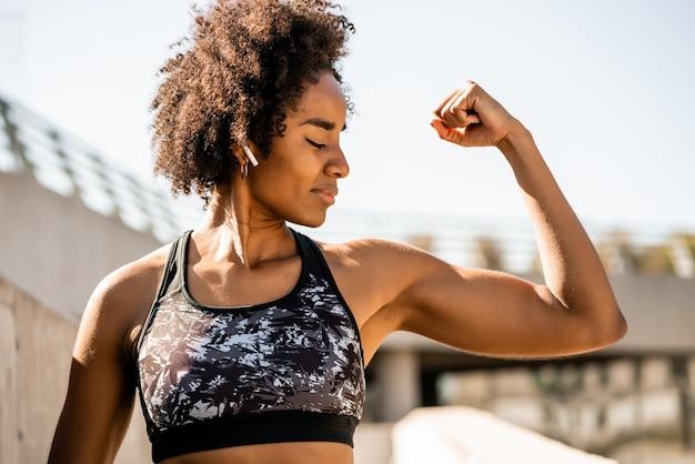 屋外に立っているときに曲がって筋肉を見せているアフロアスリートの女性の肖像画。スポーツと健康的なライフスタイル。