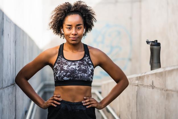 屋外で運動した後にリラックスしたアフロアスリート女性の肖像画