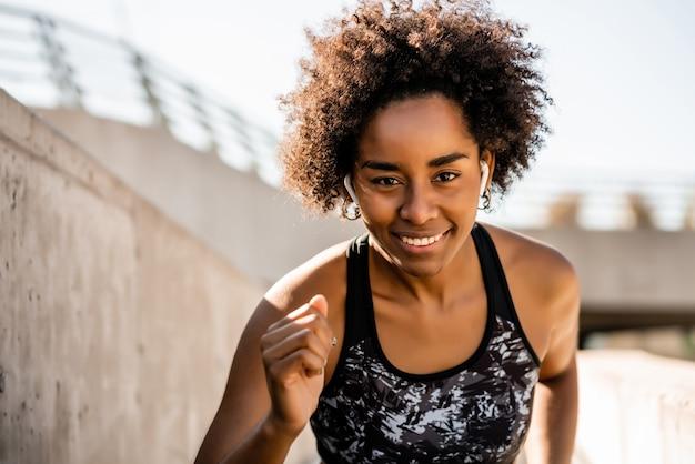 屋外で実行し、運動をしているアフロアスリート女性の肖像画。スポーツと健康的なライフスタイル。