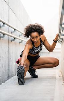 屋外で運動する前に足を伸ばしているアフロアスリートの女性の肖像画。スポーツと健康的なライフスタイル。