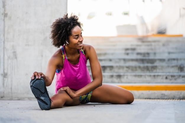 屋外で運動する前に足を伸ばしているアフロアスリート女性の肖像画。