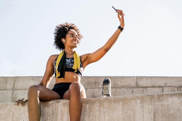 彼女の携帯電話でselfieを取り、屋外で運動した後にリラックスするアフロアスリート女性の肖像画
