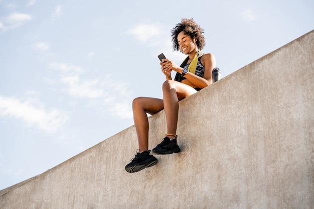 携帯電話を使用して屋外で運動した後にリラックスしたアフロアスリートの女性の肖像画。スポーツと健康的なライフスタイル。