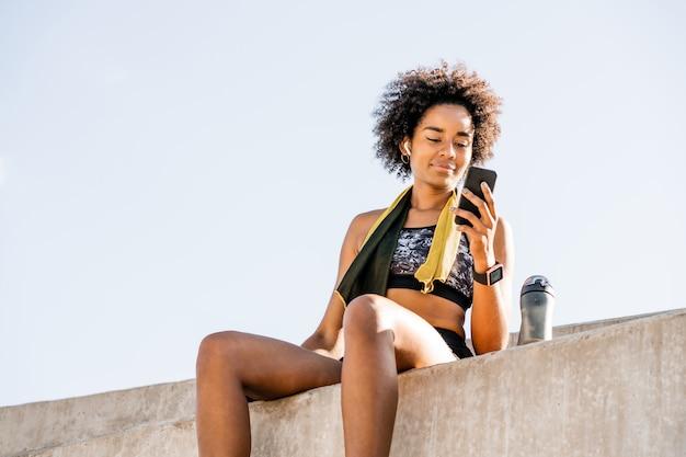 携帯電話を使用して屋外で運動した後にリラックスしたアフロアスリート女性の肖像画