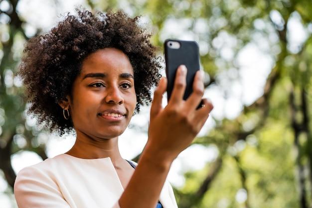 公園で屋外に立っている間携帯電話でビデオ通話をしているアフロビジネス女性の肖像画