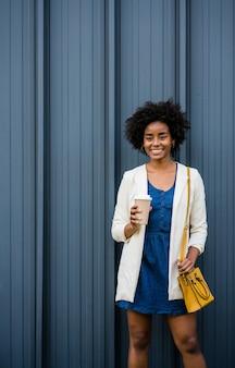 通りで屋外に立っている間コーヒーを保持しているアフロビジネス女性の肖像画。ビジネスと都市のコンセプト。