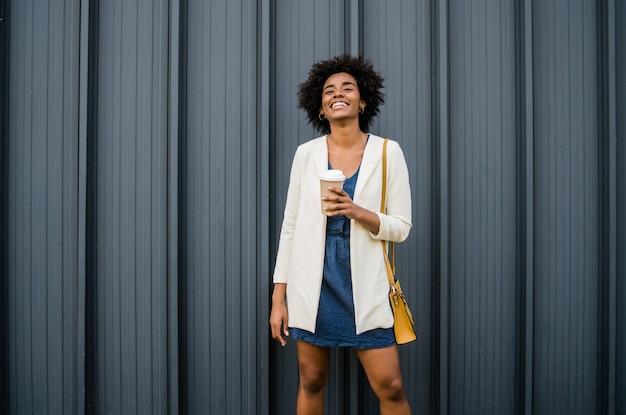 通りに屋外に立っている間コーヒーを保持しているアフロビジネス女性の肖像画