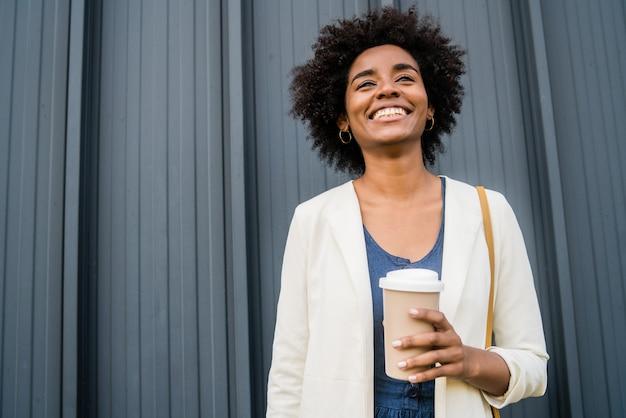Портрет афро деловой женщины, держащей чашку кофе, стоя на улице на улице