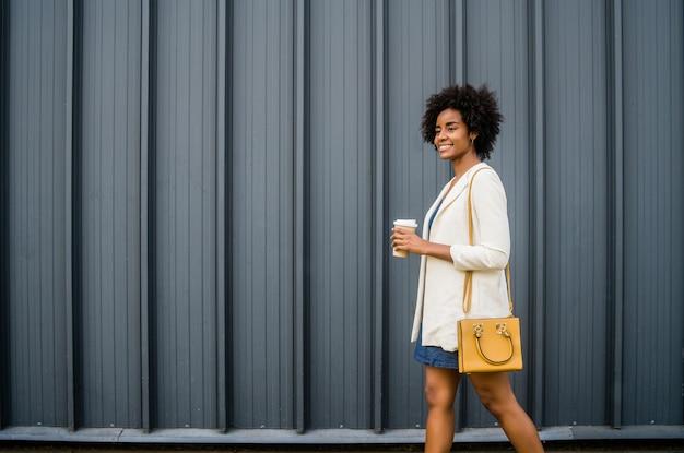 通りを屋外で歩きながらコーヒーを持っているアフロビジネス女性の肖像画。ビジネスと都市のコンセプト。