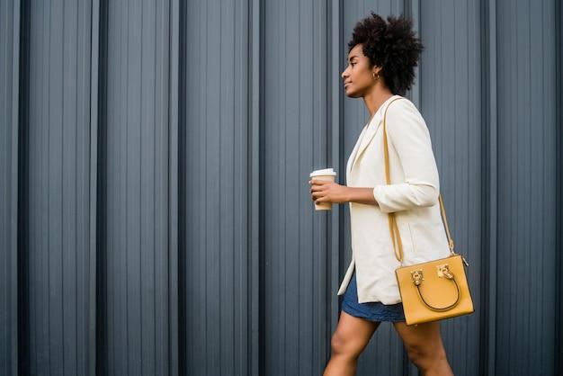 通りを屋外で歩いている間コーヒーを保持しているアフロビジネス女性の肖像画。ビジネスと都市のコンセプト。