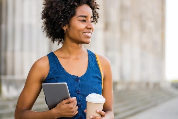 通りに屋外で立っている間、デジタルタブレットとコーヒーを持っているアフロビジネス女性の肖像画。ビジネスと都市のコンセプト。