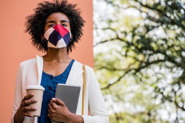 거리에 야외에서 서있는 동안 디지털 태블릿과 커피 한 잔을 들고 아프리카 비즈니스 여자의 초상화