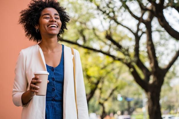 路上で屋外に立っている間笑顔でコーヒーを持ってアフロビジネス女性の肖像画。ビジネスと都市のコンセプト。