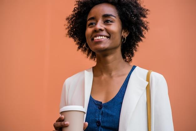 야외에서 거리에 서서 커피 한 잔을 들고 웃고 있는 아프리카 비즈니스 여성의 초상화. 비즈니스 및 도시 개념입니다.