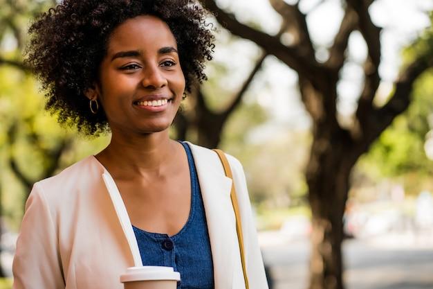야외에서 거리에 서서 커피 한 잔을 들고 웃고 있는 아프리카 비즈니스 여성의 초상화
