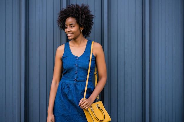 路上で屋外に立って笑っているアフロビジネス女性の肖像画。ビジネスと都市のコンセプト。