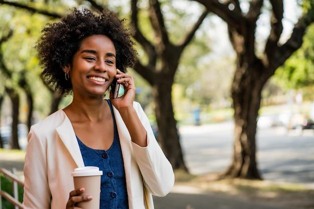 야외에서 공원에 서 있는 동안 전화 통화를 하고 커피 한 잔을 들고 있는 아프리카 비즈니스 여성의 초상화. 비즈니스 개념입니다.