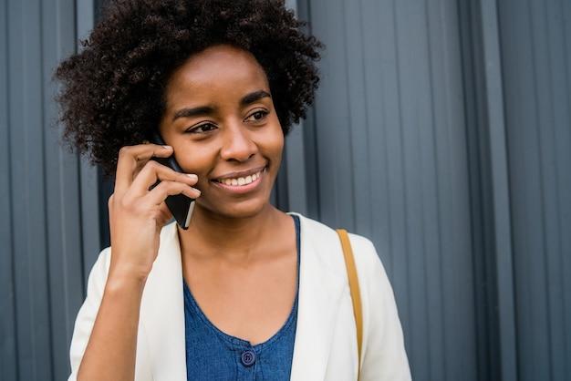 電話で話し、通りで屋外に立っている間コーヒーを保持しているアフロビジネス女性の肖像画