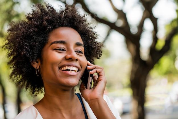 야외 공원에 서 있는 동안 전화 통화 하는 아프리카 비즈니스 여자의 초상화. 비즈니스 개념