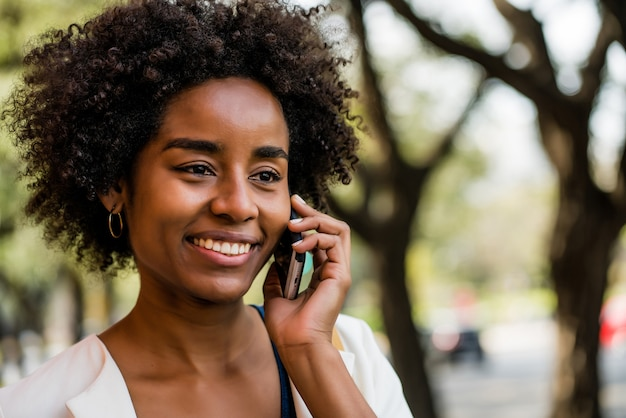 야외 공원에 서 있는 동안 전화 통화 하는 아프리카 비즈니스 여자의 초상화