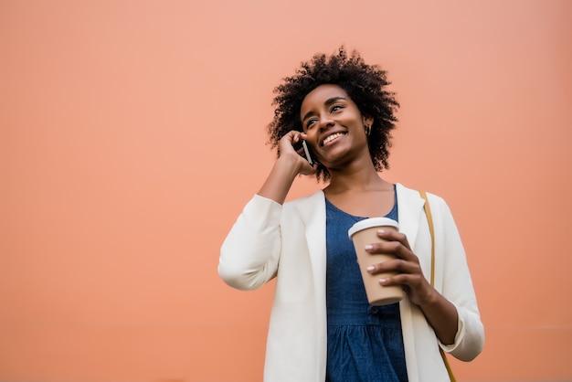 야외 거리에 서있는 동안 전화 통화하는 아프리카 비즈니스 여자의 초상화. 비즈니스와 도시 개념.