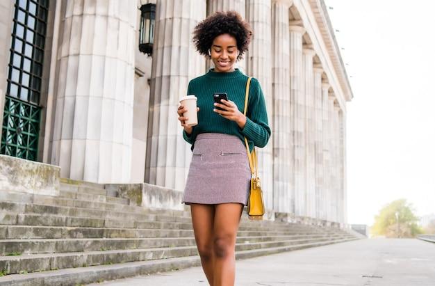 彼女の携帯電話を使用して、通りで屋外を歩いている間コーヒーを持っているアフロビジネス女性の肖像画。ビジネスと都市のコンセプト。