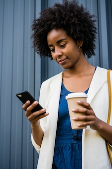通りで屋外に立っている間彼女の携帯電話を使用してアフロビジネス女性の肖像画。ビジネスと都市のコンセプト。 Premium写真