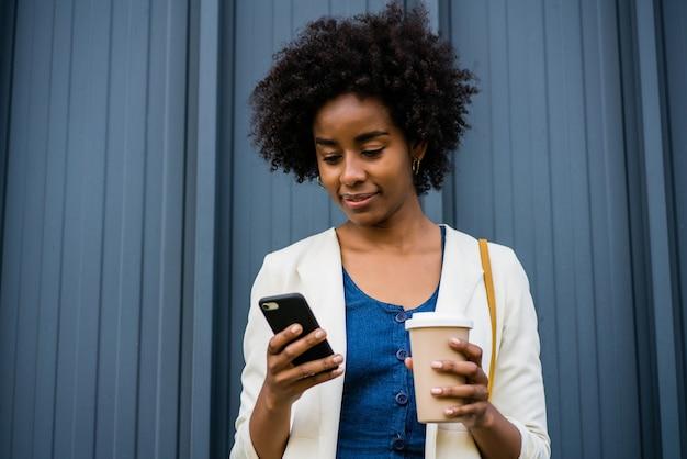 通りで屋外に立っている間彼女の携帯電話を使用してアフロビジネス女性の肖像画。ビジネスと都市のコンセプト。