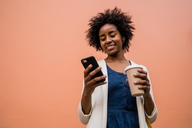 거리에 야외에서 서있는 동안 그녀의 휴대 전화를 사용하는 아프리카 비즈니스 여자의 초상화