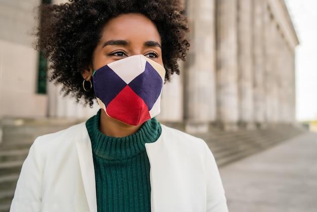 通りで屋外に立っている間保護マスクを身に着けているアフロビジネス女性の肖像画。ビジネスと都市のコンセプト。
