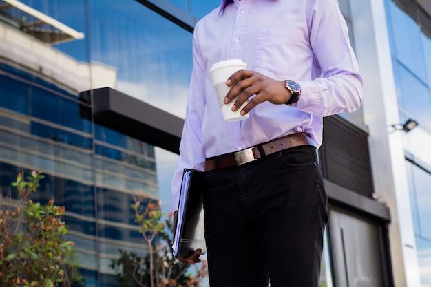 仕事から休憩を取って、屋外で一杯のコーヒーを飲むアフロのビジネスマンの肖像画。ビジネスコンセプトです。