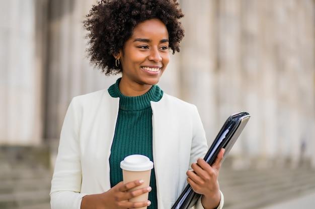 通りで屋外を歩いている間、コーヒーとクリップボードを持っているアフロ実業家の肖像画。ビジネスと都市のコンセプト。