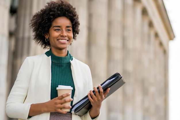 通りで屋外を歩いている間コーヒーとクリップボードを保持しているアフロ実業家の肖像画。ビジネスと都市のコンセプト。