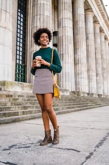 通りで屋外を歩いている間コーヒーを保持しているアフロ実業家の肖像画。ビジネスと都市のコンセプト。